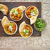 Hähnchencurry mit Reis, Naan-Brot, Raita und Koriandergrün (Indien)