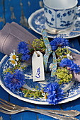 A small wreath of cornflowers, lady's mantle, and chamomile as a plate decoration