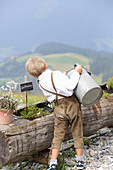 A little boy wearing lederhosen watering herbs on a mountain