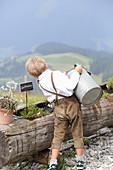 Kleiner Junge in Lederhose gießt Kräuter auf der Alm