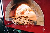 Pizza Bianco in den Holzofenschieben
