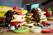 Pancakes with kiwi, strawberries, banana, chocolate and pistachios