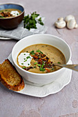 Creamy mushroom soup with baked bread and fresh parsley