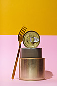 Three tins and a fork against a pink and yellow background