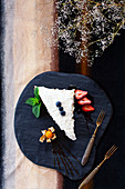 A slice of coconut cake with berries and physalis