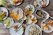 Essensreste und benutztes Geschirr vom Grillfest