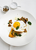 Fried egg, with mushrooms on white crusty toast, with sage, black pepper and salt in white bowls