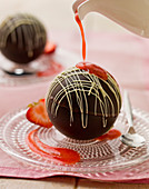 Chocolate spheres with melting hot strawberry sauce being poured from a white jug, on a glass plate and spoon