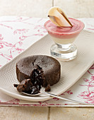 A chocolate souffle with molten chocolate inside and a strawberry mousse with a white chocolate wafer
