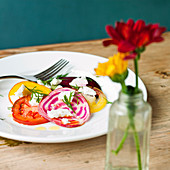 Tomato, red onion and beetroot salad, with goats cheese and dill