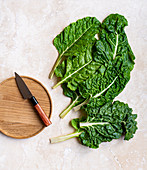 Spinach leaves with wooden board and knife