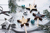 Shortbread stars on sticks filled with jam and decorated with chocolate glaze