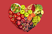 Various vegetables, fruit, nuts in heart shape on red background with clipping path