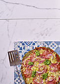 Green broccoli and spinach base pizza with salami and pesto