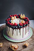 A white chocolate cake decorated with berries and physalis