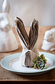 Easter place setting with folded linen napkin and succulent