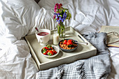 Breakfast in bed with fruit tea, granola, milk and strawberries