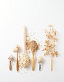Haferähre, Haferkörner, Haferflocken, Porridge und Hafermehl auf Löffeln