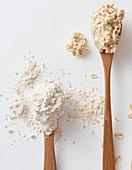 Porridge und Hafermehl auf Holzlöffeln