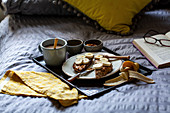 Breakfast in bed with tea, honey, peanut butter and toast