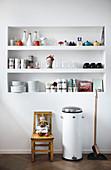 Geschirr und Küchenutensilien im eingebauten Regal in weißer Wand