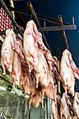 Rohe gerupfte Pekingenten hängen auf einem Markt