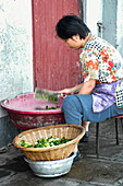 Woman chopping vegetable on a Chinese market