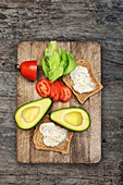 Bread with herb quark, avocado, tomatoes and lettuce on a chopping board