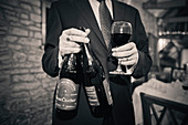 Man holding Wine Glass and Two Bottles of Red Wine at Wedding