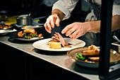 Koch richtet Essen auf Teller an