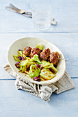 A meatball skewer with pointed cabbage