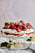 Pavlova cake with fresh strawberries garnished with fresh mint leaves and elderflower