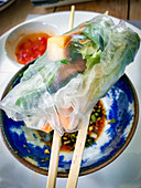 A Vietnamese spring roll on chopsticks