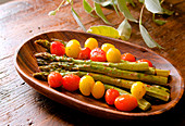 Green asparagus with cherry tomatoes, soy sauce and lemon being prepared