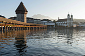 The Kapellbrücke (Chapel Bridge) over the River Reuss with the water tower and the Jesuit Church, Lucerne, Switzerland