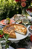 Pikanter Knoblauch-Käsekuchen auf sommerlichem Tisch im Freien