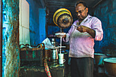 A man making a turmeric chai latte in a street kitchen (India)
