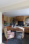 Sessel am alten Holztisch in der Küche mit rostigen Fronten