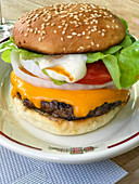 A cheeseburger with onions, tomato and mayonnaise