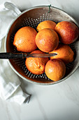 Blood oranges in a colander with a knife