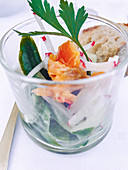 Cucumber salad with radishes and salmon in a glass