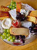 A cheese platter with crackers and grapes