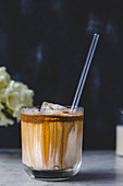Iced coffee latte in a glass with a straw