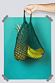 Hand carrying net bag with ripe pineapple and bananas against blue turquoise rectangle during zero waste shopping