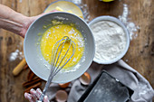 Whipping eggs in black bowl on wooden table with lemon, flour, butter and cinnamon sticks ingredients for cake