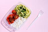 Gesunde Lunchbox mit Tomaten, Zucchininudeln und Reis