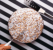 Cutting whole cake with icing sugar and nuts on black and white striped surface