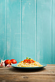 Blue ceramic plate with pasta and tomato sauce decorated with parsley on a wooden table with light blue wooden background