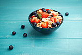 Breakfast bowl of corn flakes with strawberries and blueberries on wooden blue background