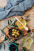 Organic olive oil in a glass with olive branches and green and black olives